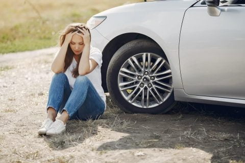Women sitting beside broken car